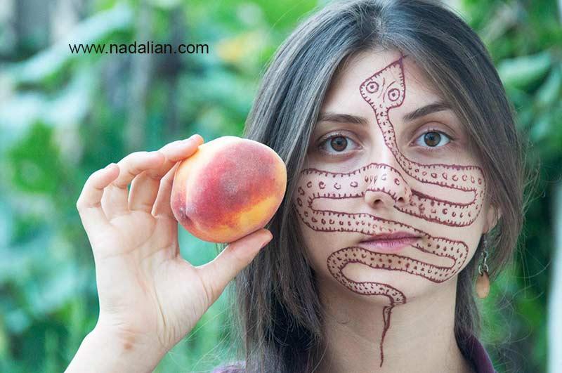 طراحی نقش مار بر روی چهره دختر گرجستانی با خاک سرخ جزیره هرمز