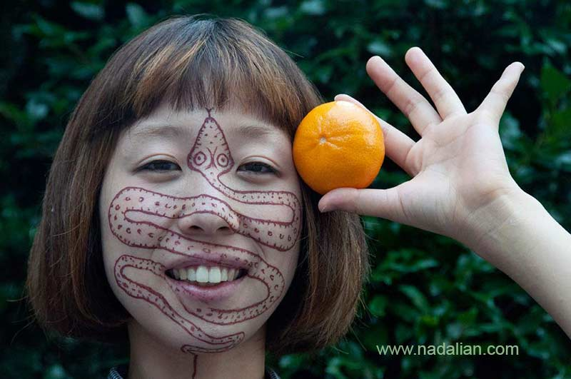 طراحی نقش مار بر روی چهره دختر ژاپنی با خاک سرخ جزیره هرمز