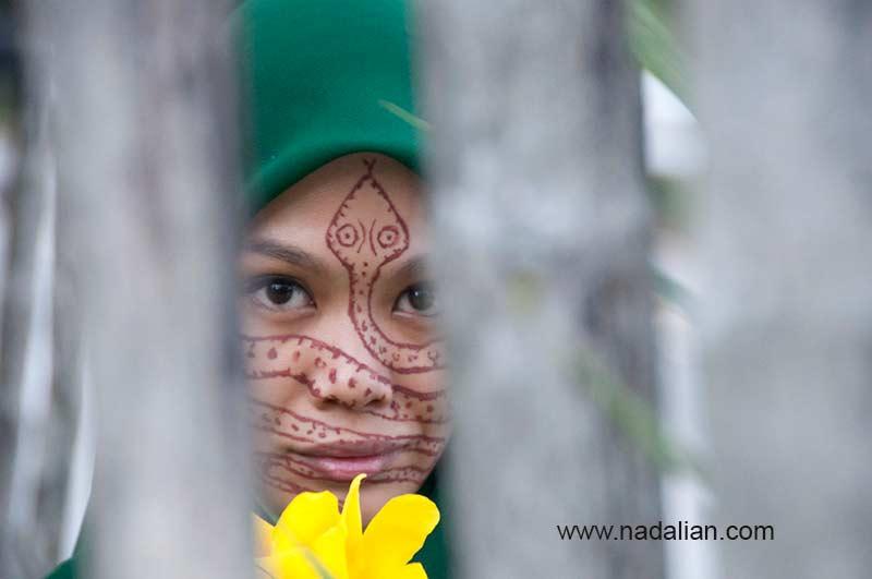 طراحی نقش مار بر روی چهره دختر مالزیایی با خاک سرخ جزیره هرمز