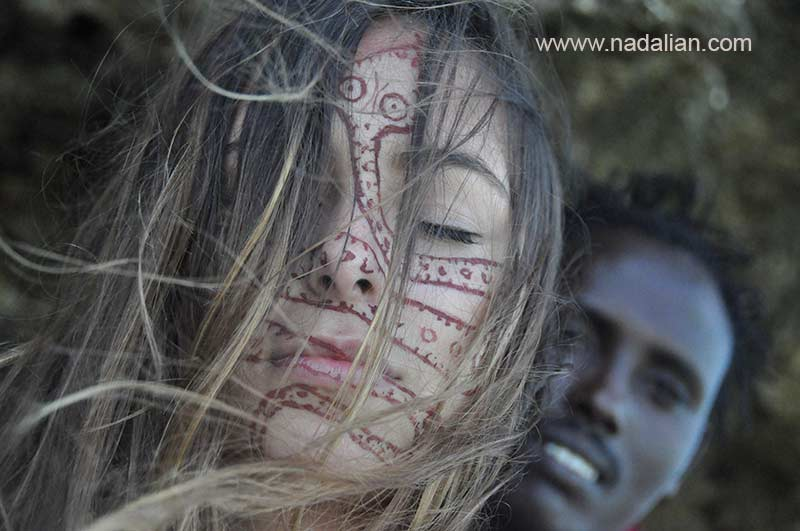 Design on the face of girls from USA by red earth of Hormuz Island