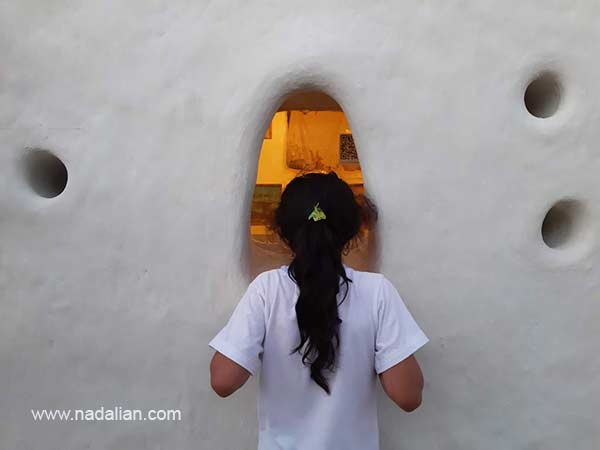 دختری از لاقت نقاشی های داخل را از پنجره کوچک تماشا می کند، ورودی خانه دکتر نادعلیان در بندر تاریخی لافت