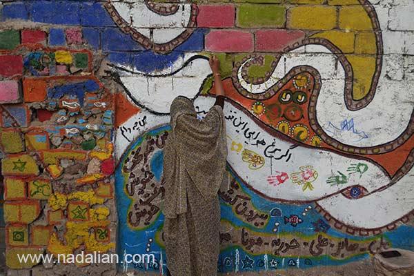 Girl Painting on the wall, near Dr Nadalian Museum, Hormouz_Island