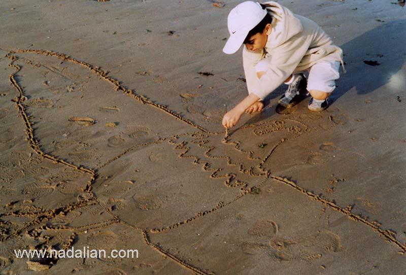 پسرم بهزاد نادعلیان در حال طراحی یک مرغ دریایی بر روی ماسه ها جزیره قشم