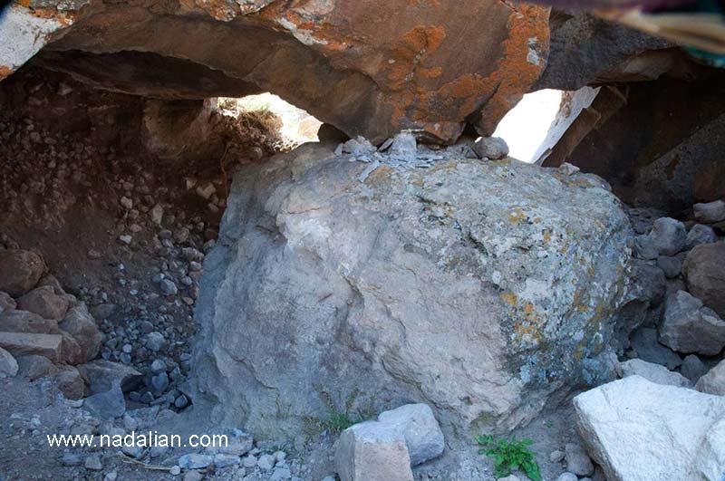 قسمت زیزین صخره بزرگی که هنرمندان بین المللی در حال بازدید و عکاسی از آن هستند محل حفاری شده است