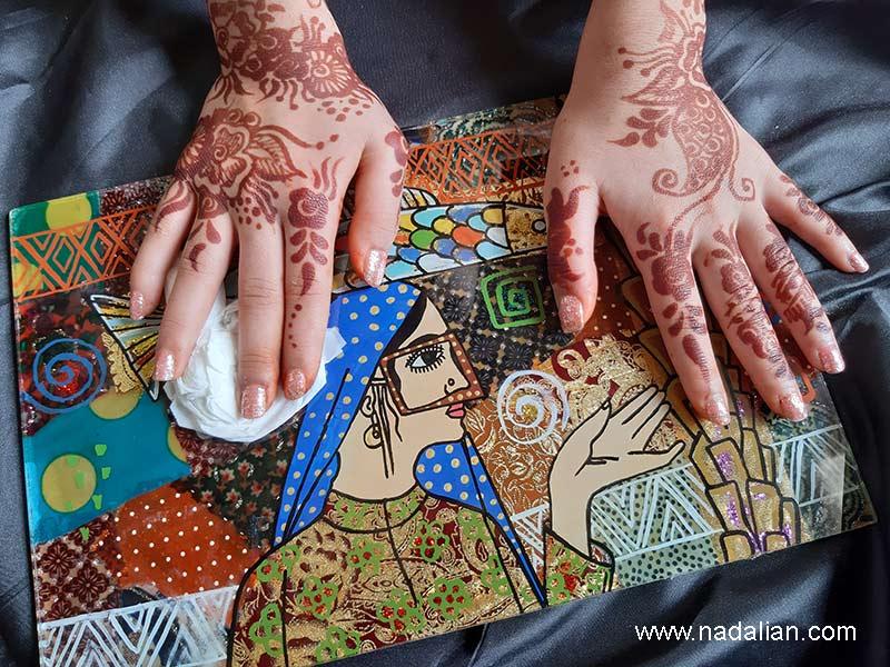 دختر در حال تمیز کردن پارچه نقاشی پشت شیشه، طرح احمد نادعلیان و اجرا دختران در بکی از روستاهای قشم