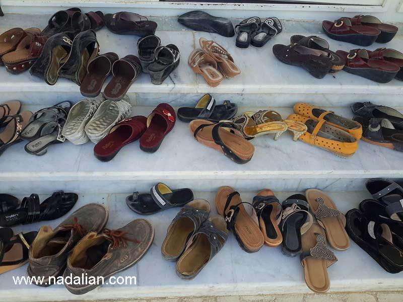 کفش های احمد نادعلیان و همسرش در کنار سندل های دختران و زنان در بندر تاریخی لافت قشم، محل آموزش پارچه نقاشی پشت شیشه