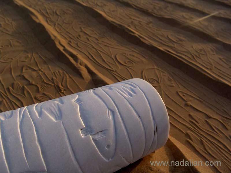 چاپ نقش الهه ها و ماهی با استفاده از مهر های استوانه ای احمد نادعلیان بر روی ماسه ساحل دریا، چزیره هرمز