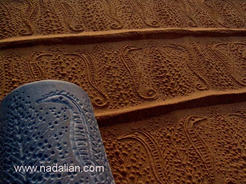 چاپ نقش اسب های دریایی با استفاده از مهر های استوانه ای احمد نادعلیان بر روی ماسه ساحل دریا، چزیره هرمز