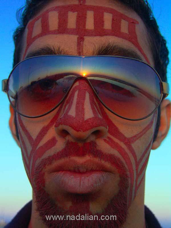 """نقاشی با خاک سرخ جزیره هرمز، بر روی چهره ای یکی از آقایان شرکت کننده در کارگاه، ساحل """"مغ ناخا"""" بندر عباس"""