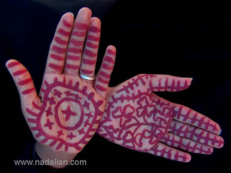 """نقاشی با خاک سرخ جزیره هرمز، بر روی دستهای یکی از دختران شرکت کننده، در ساحل """"مغ ناخا"""" بندر عباس"""
