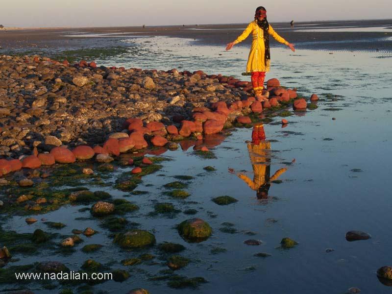 """ساحل """"مغ ناخا"""" بندر عباس نقاشی با خاک سرخ بر روی دستها و چهره ای یکی از دختران شرکت کننده در کارگاه و همچنین نقاشی سنگهای کنار ساحل با خاک سرخ"""
