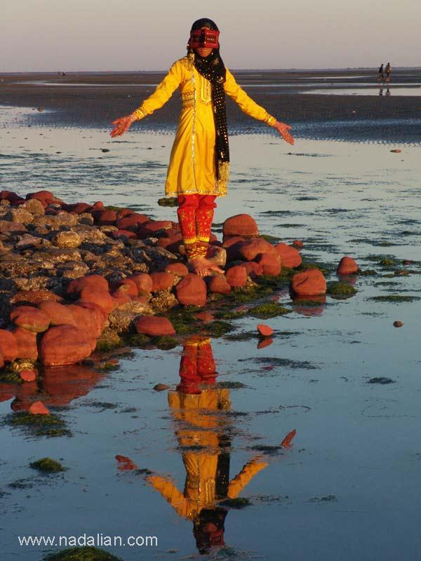 """ساحل """"مغ ناخا"""" بندر عباس نقاشی با خاک سرخ بر روی دستها و چهره ای یکی از دختران شرکت کننده در کارگاه"""