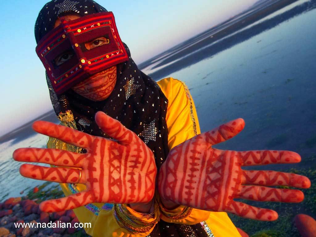 """نقاشی با خاک سرخ جزیره هرمز، بر روی دستها و چهره ای یکی از دختران شرکت کننده، در ساحل """"مغ ناخا"""" بندر عباس"""